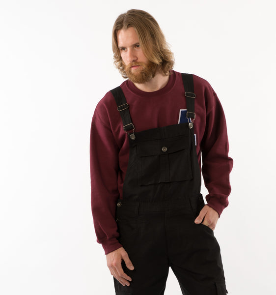 'Bill Black' style bib overalls paired with maroon sweater and left hand in front pocket.