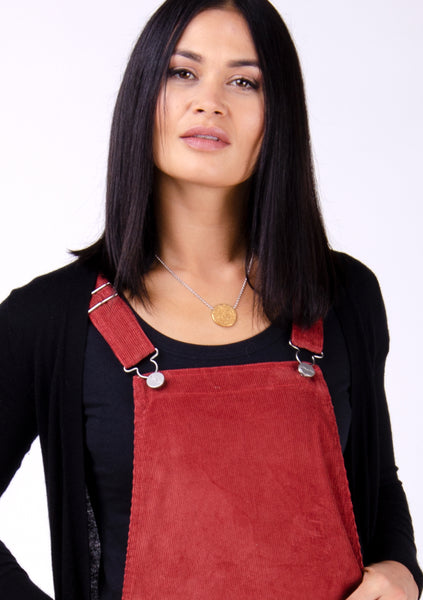 Red cord dungaree dress with focus on adjustable straps, paired with black cardigan and t-shirt.