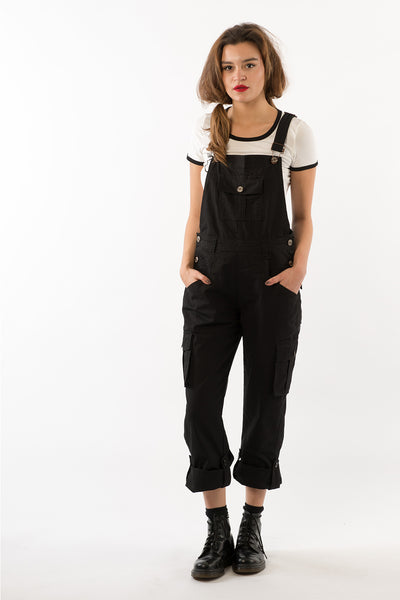 Full-length shot of model with hands in front pockets of black denim dungarees with cargo pockets and turned up trousers.