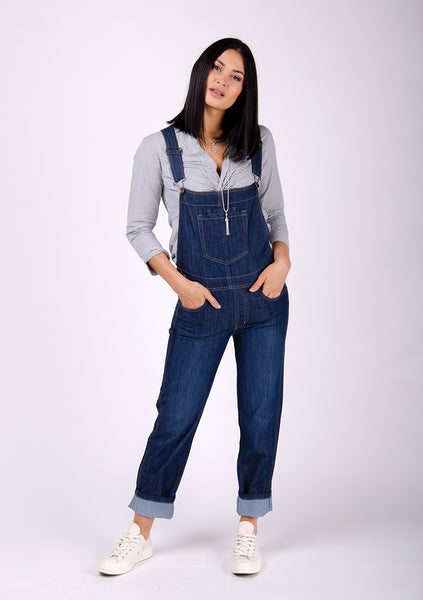 Women's 'Dottie' brand denim dungarees turn-ups. Model with hands in front pockets and paired with light trainers and grey blouse.