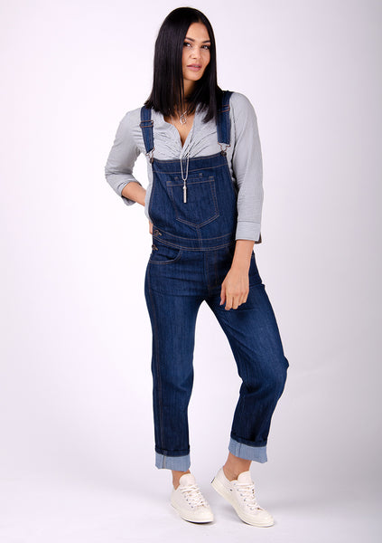 Ladies denim dungarees paired with grey blouse and white pumps.