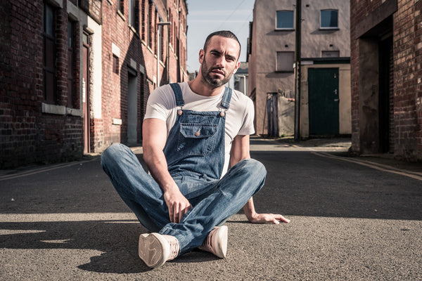 Man sat cross-legged in the middle of a narrow suburban road, wearing blue denim dungarees with white t-shirt.