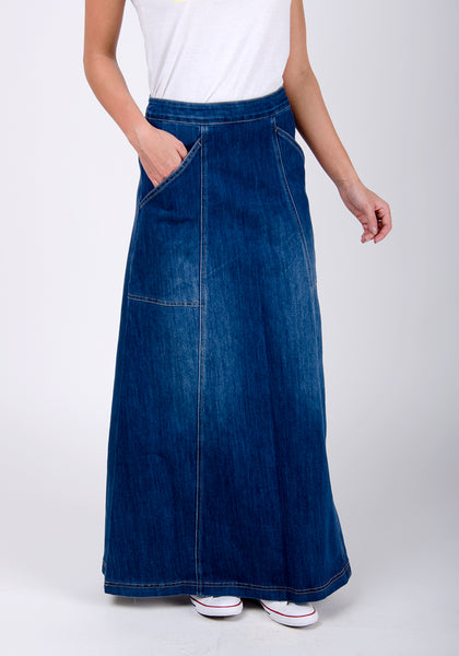 Ankle-length maxi-denim skirt with hand in right pocket.