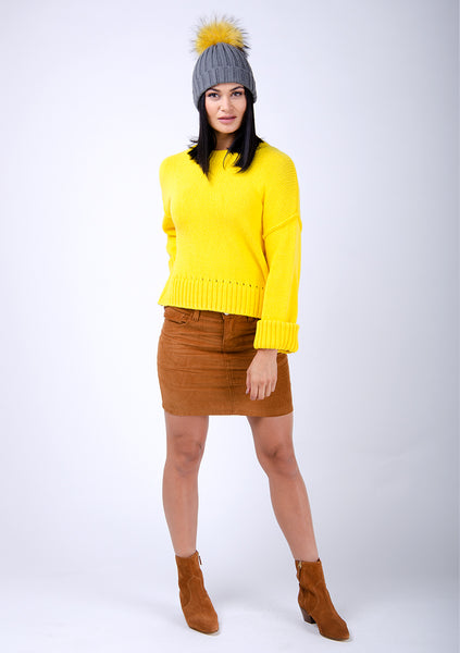 Brown cord mini skirt paired with bright yellow knit sweater and cute bobble hat.