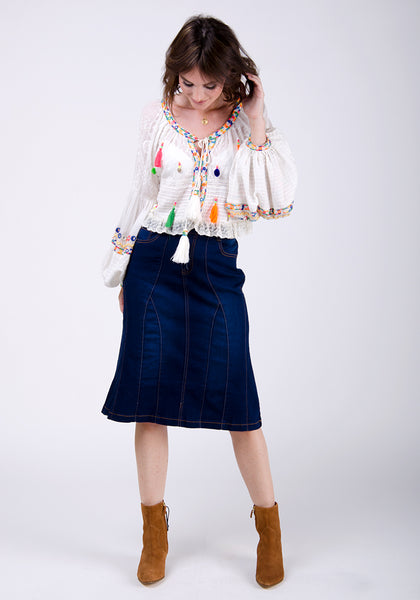 Indigo denim midi-skirt styled with tan suede boots and white frilly blouse.