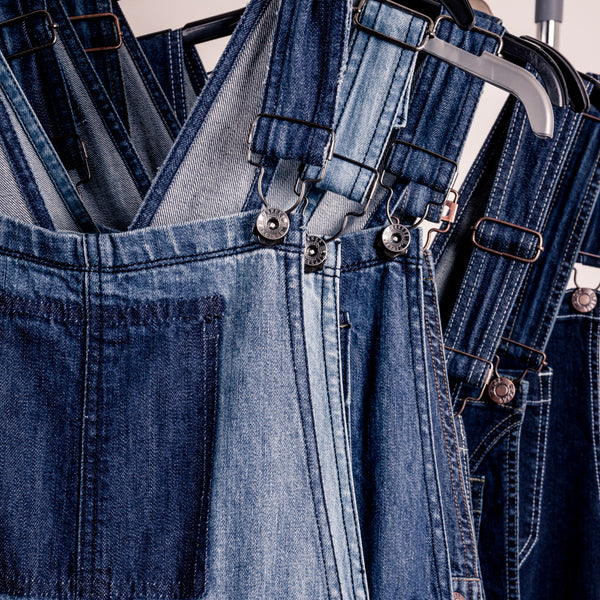 Various denim dungarees on a rail.