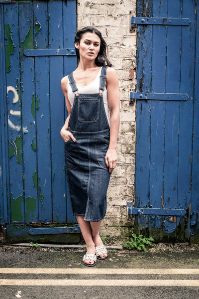 'Skylar' style midi dark-wash dungaree dress in shabby urban alley.