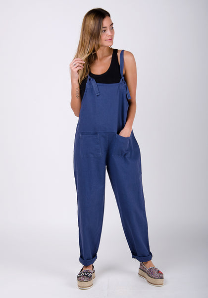 Blue linen dungaree all-in-one jumpsuit for women with hand in left pocket.