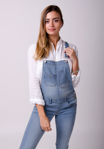 Wearing pale blue bib-overalls and holding left strap and paired with white blouse.