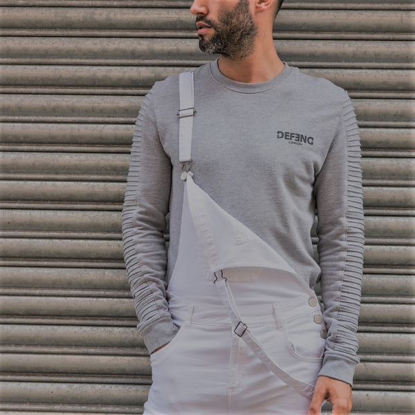 'Trafford' brand off-white biker style skinny dungarees with left strap unsecured revealing grey sweater and rear bib material.