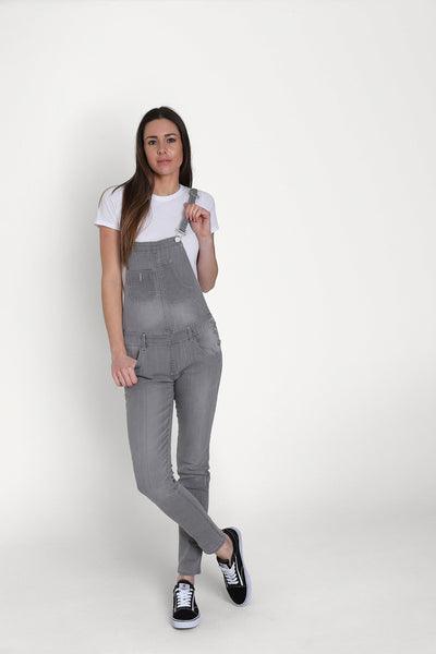 Grey 'Talia' style skinny fit dungarees for women, paired with white t-shirt and dark trainers.