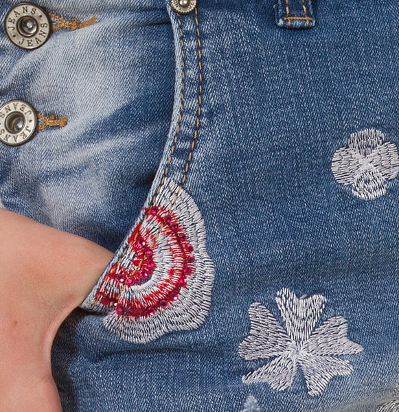 Embroidered denim dungarees close-up.