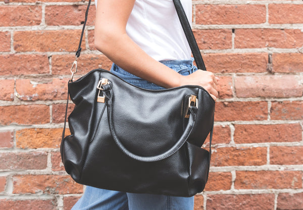 Pale wash jeans and white t-shirt with large black leather bag over right shoulder.