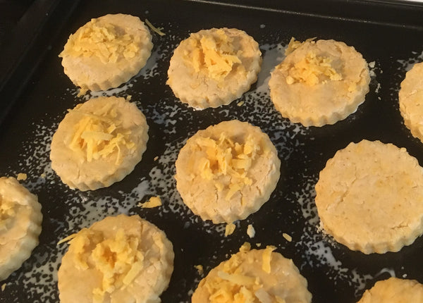 A dozen cheese scones cooling on a tray.