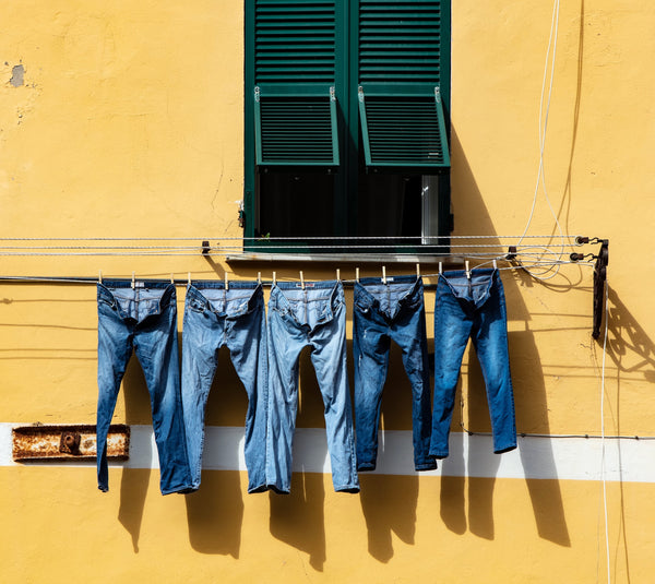 Five pairs of jeans drying on a line outdoors.