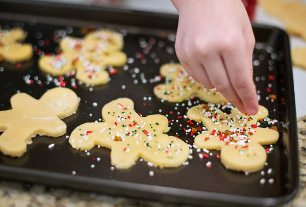 Decorating gingerbread men on a baking tray.