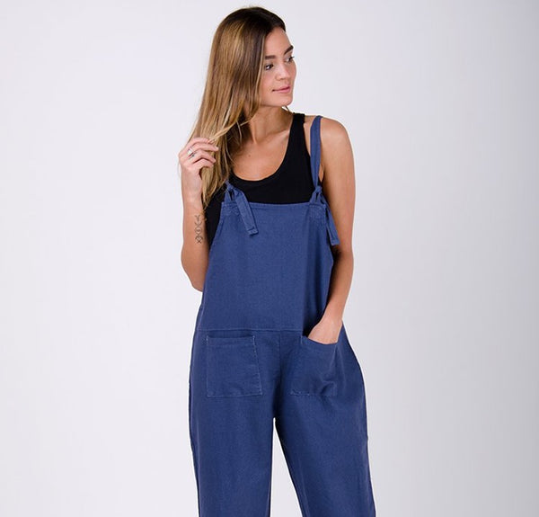Women's sky-blue oversized linen dungarees paired with black t-shirt. Model with left hand in pocket.