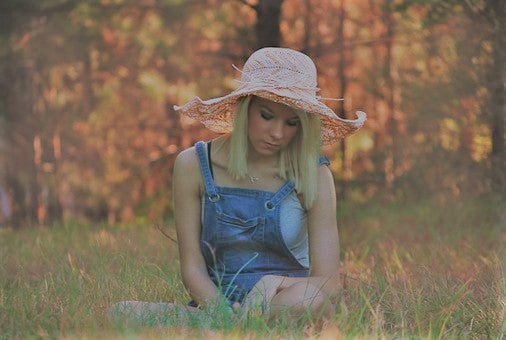 Woman sat in field wearing dungaree shorts and pink floppy hat.