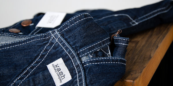 Close-up of dark denim dungarees with white stitching and Wash Clothing Company logo.