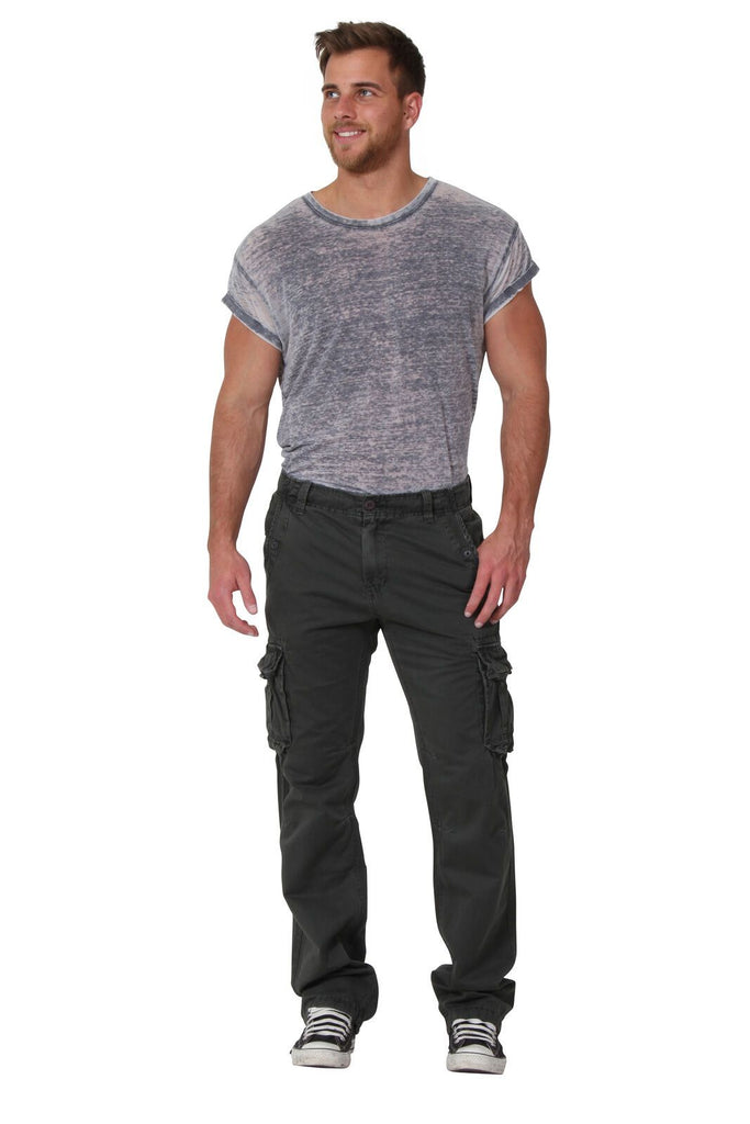 Full front view, looking to right, wearing olive, cotton-mix combat trousers with drawstring ankle.