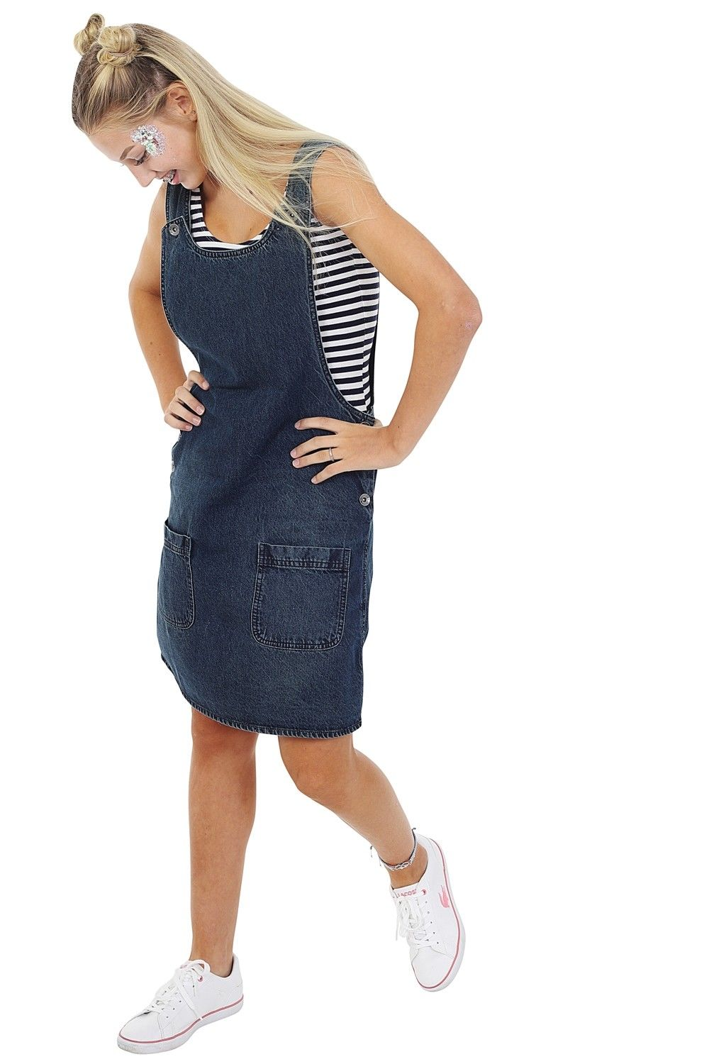 Angled front-side walking pose wearing 'Renee' style, short denim vintage wash pinafore dress with adjustable shoulder.