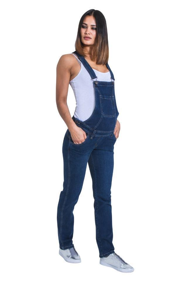 Full-frontal pose looking to her right, wearing dark wash denim overalls.