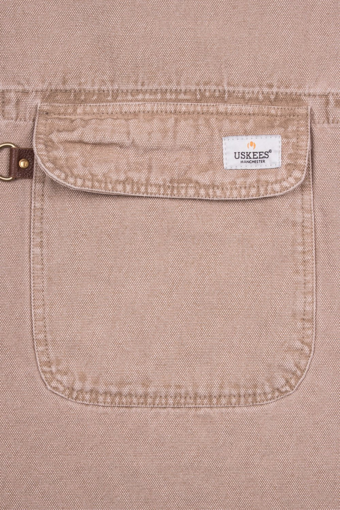 Close up of handy apron pocket with 'USKEES' sewn brand label on flap.