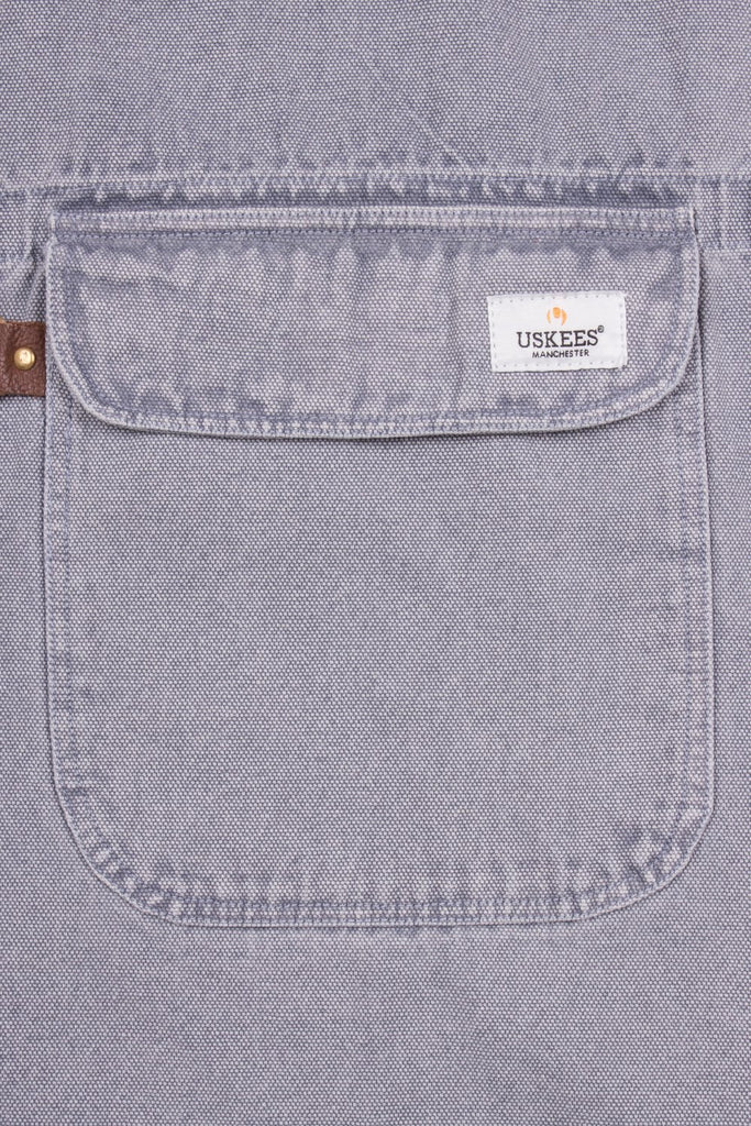 Close up of handy apron pocket with 'USKEES' sewn brand label on pocket flap.