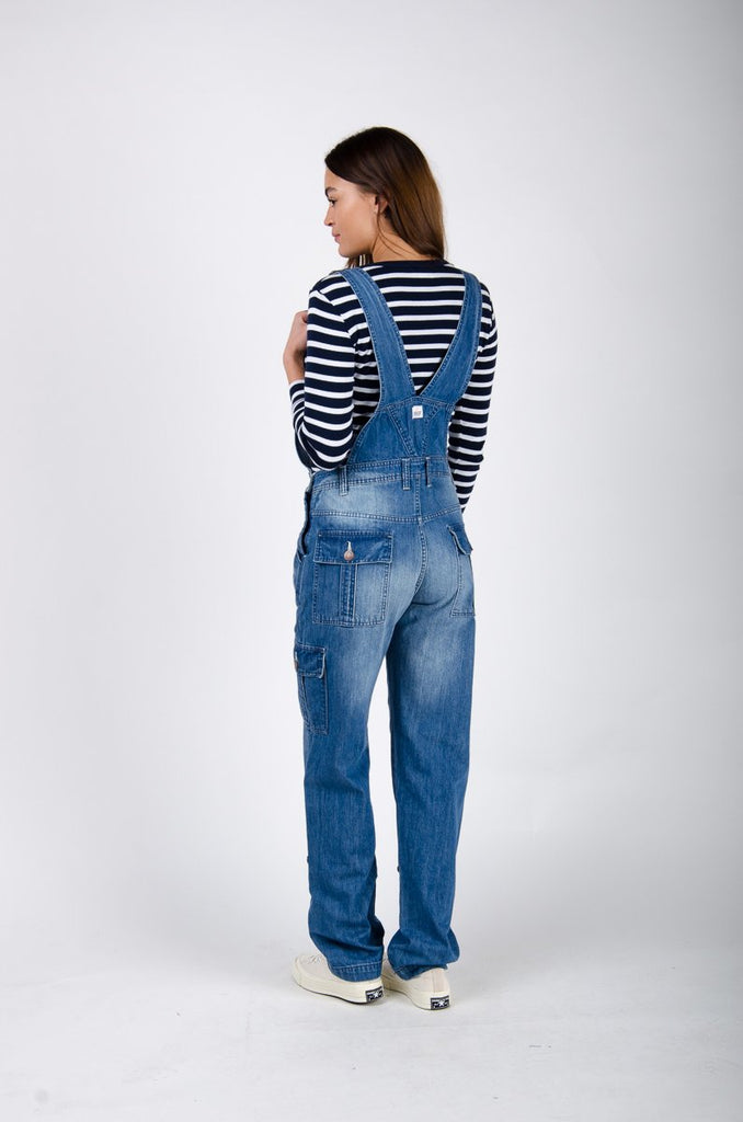 Full rear pose, focusing on adjustable straps and rear pockets on faded denim dungarees.