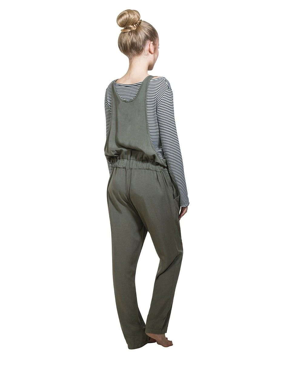 Full-length angled rear pose, wearing khaki lyocell overall and black and white hooped long-sleeved t-shirt.