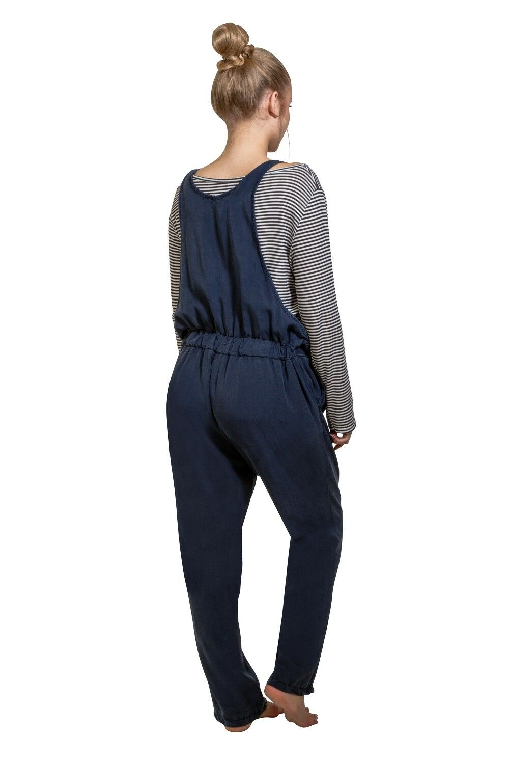 Full-length angled rear pose, wearing dark blue overall and black and white hooped long-sleeved t-shirt.