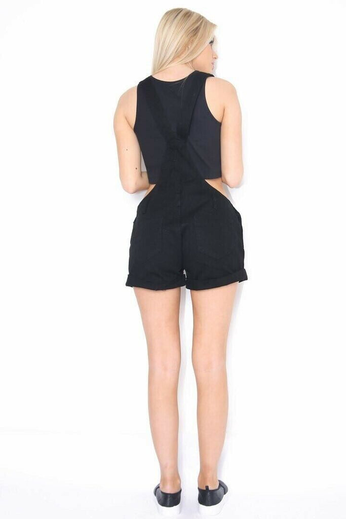 Full rear view of bib overall shorts for women with turn-up hem with rips and abrasions.