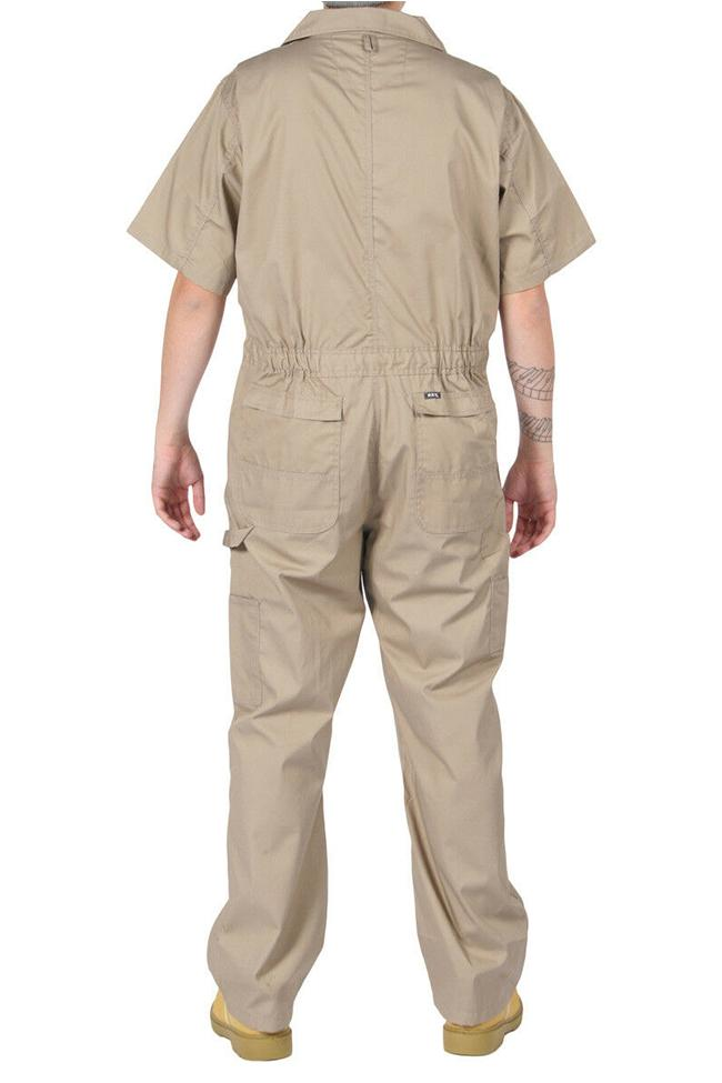Full-length front view with hands in right pocket, wearing 'Key Apparel USA' relaxed-fit khaki coverall, showing chest pockets with 'flap and snap closure'.