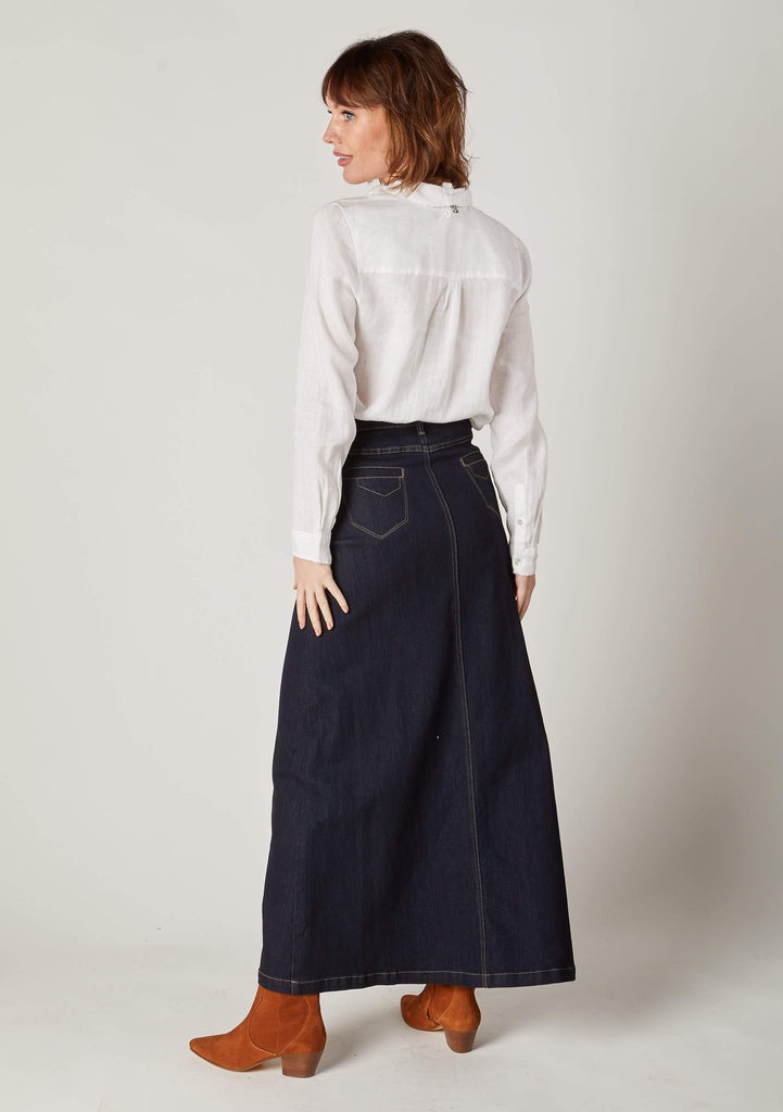 Full length, angled rear view of dark denim, ankle length denim skirt with view of back pockets.