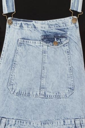 Close-up of overall bib on acid-wash overall, showing pockets and adjustable straps.