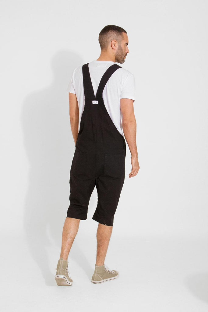 Rear view of black, slim-fit cotton dungaree-shorts with clear view of cross straps and brand label.