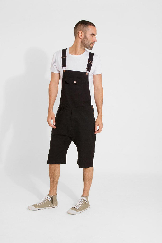 Diagonal-front view of black 'Jesse' style slim dungaree, styled with white t-shirt and khaki Converse shoes.