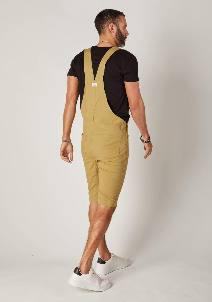 Rear-diagonal view of khaki, slim-fit cotton dungaree-shorts with clear view of cross straps and brand label.