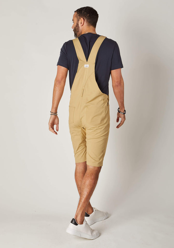 Rear-diagonal view of sand, slim-fit cotton dungaree-shorts with clear view of cross straps and brand label.
