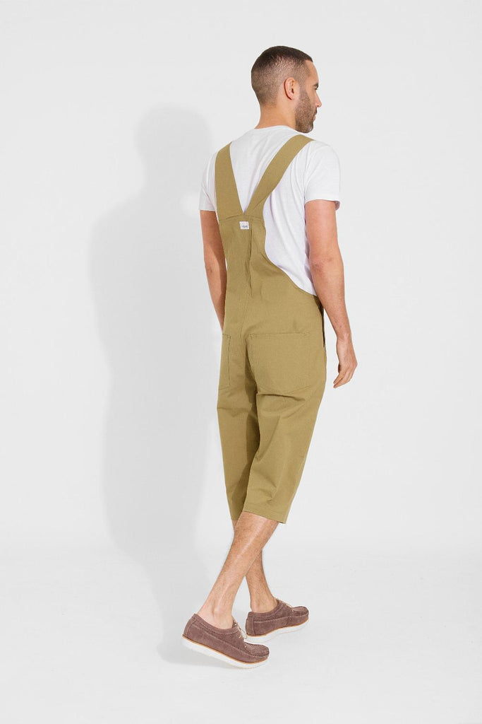 Rear-diagonal view of olive, slim-fit cotton dungaree-shorts with clear view of cross straps and brand label.