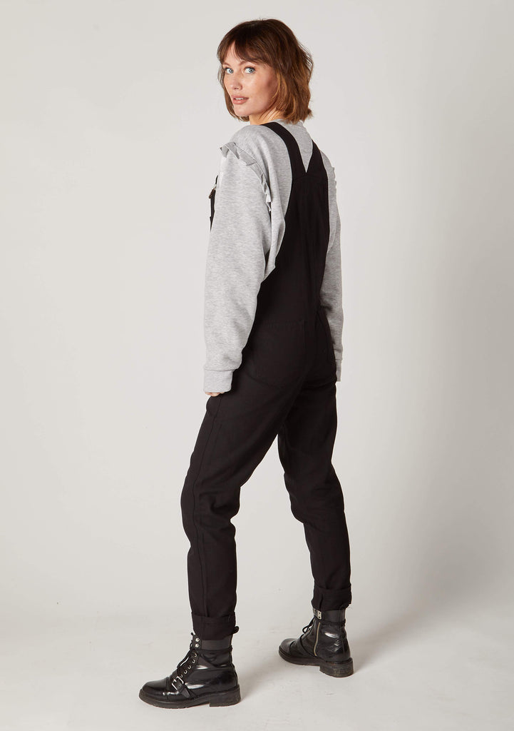Full side pose facing to her right wearing 'Amanda' brand Womens Carrot Fit Black Dungarees.