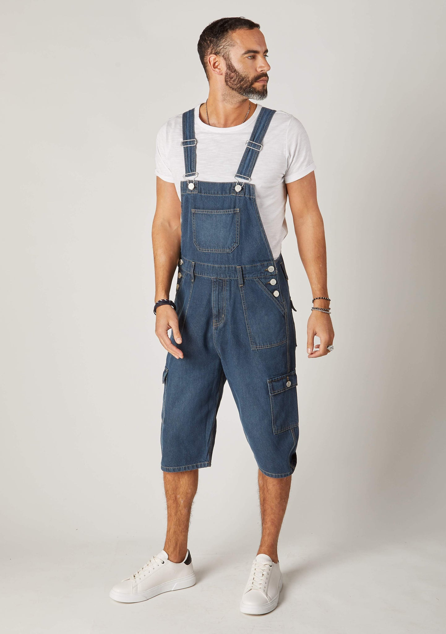Full slightly angled frontal pose looking to left wearing dungarees shorts for men with focus on adjustable straps.