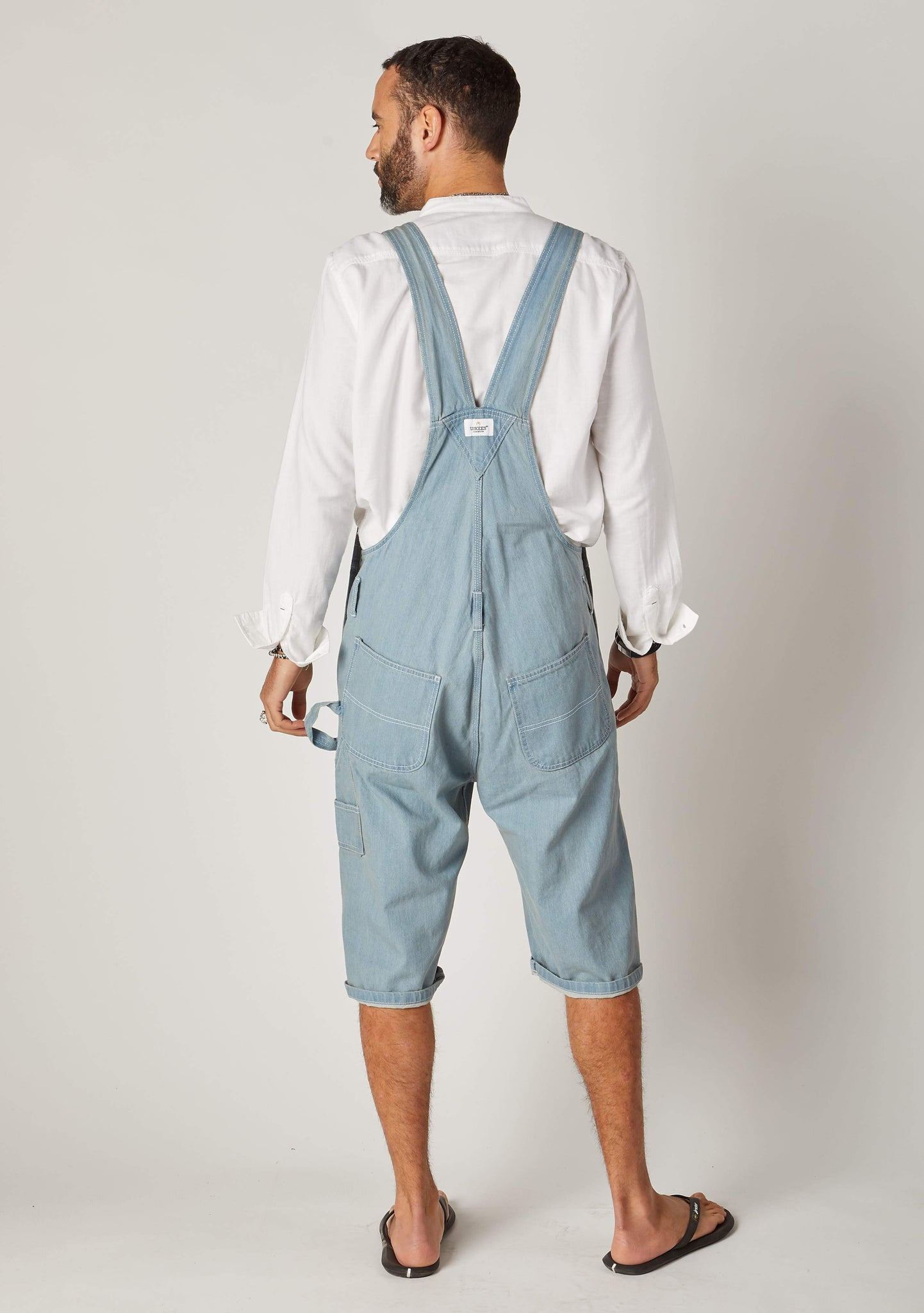 Rear pose looking left, wearing 'Blake' brand pale wash bib overalls shorts from Dungarees Online.