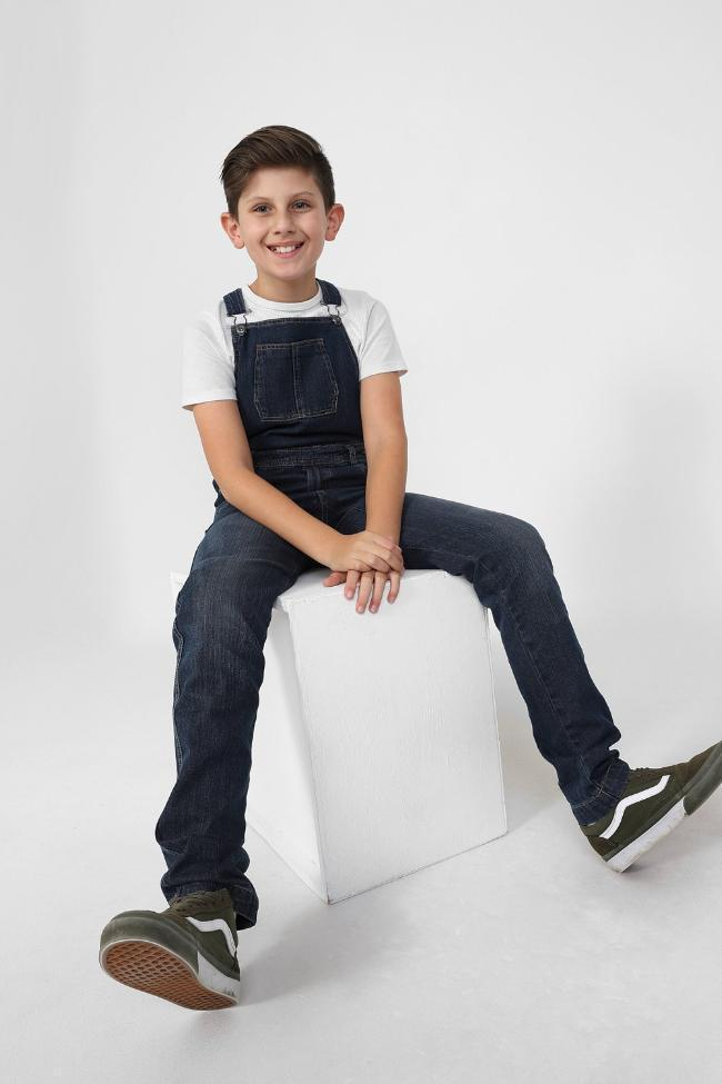 Boy sitting on box with stretched legs, wearing dungarees with adjustable straps.