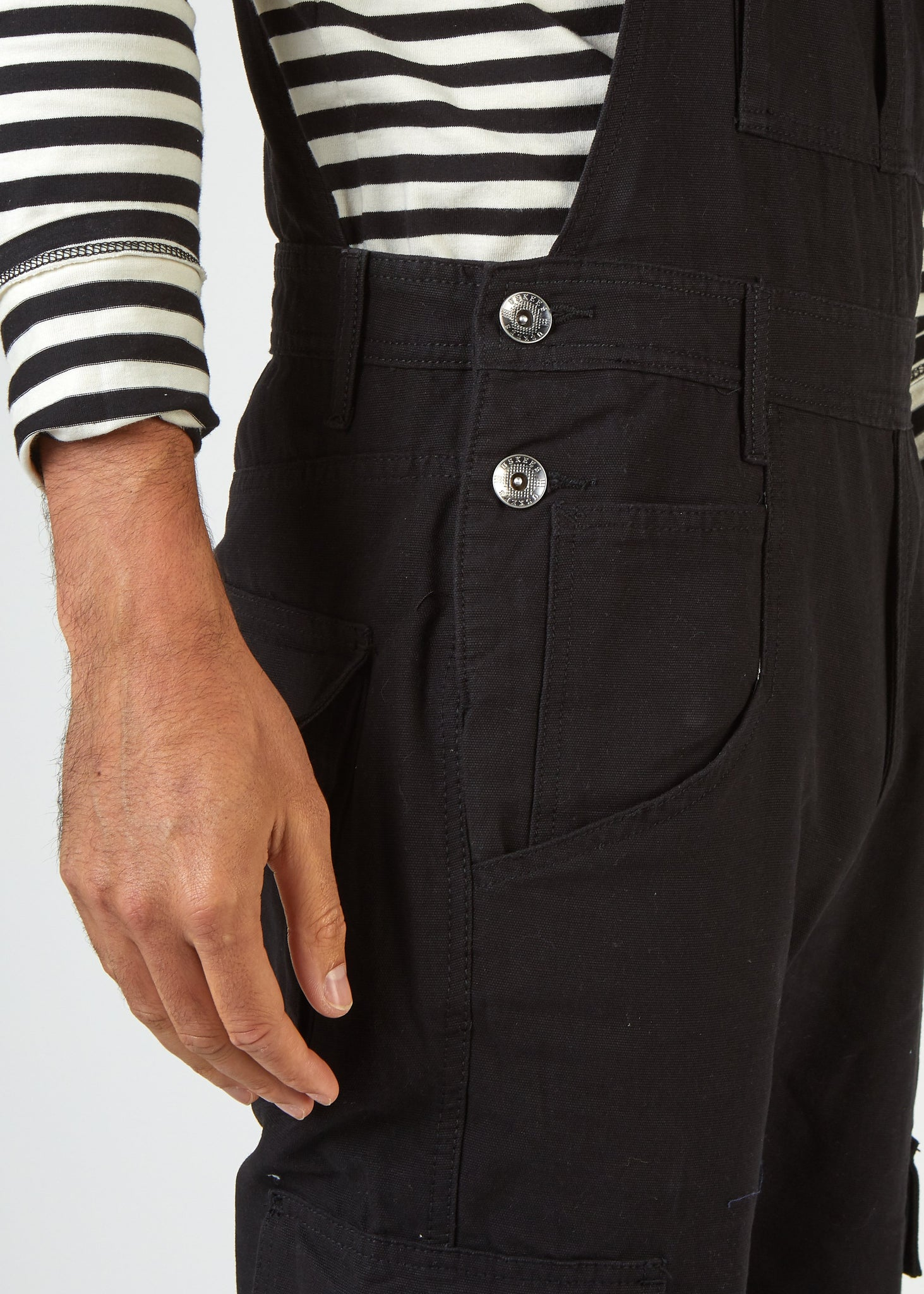 Focus on mid region of Bill black dungarees with focus on 2-button side closure and side pockets.