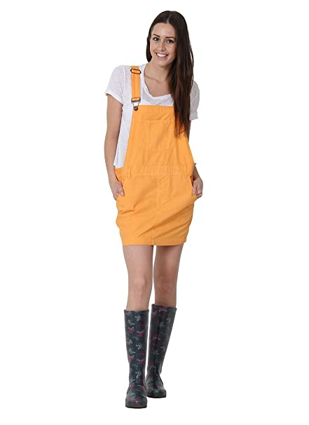 Full-length frontal view of 'Claire' oversized orange dungaree dress with hands in front pockets and view of adjustable straps.