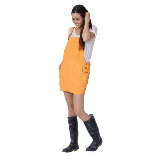 Full-length, angled side-front view of loose fit gold-orange bib-overall dress with view of one-side button fastening and bib pocket