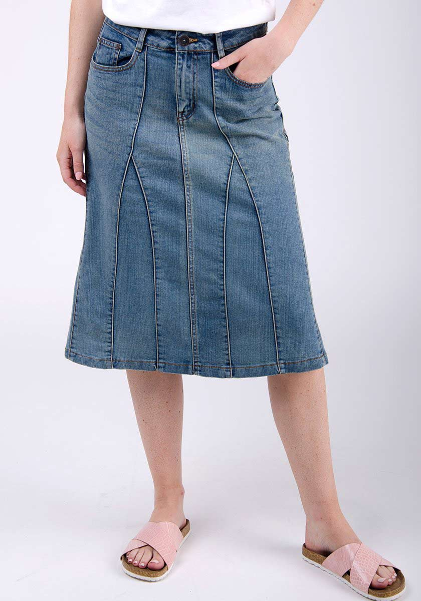 Half-front pose focussing on front pockets, panels and zip styling of knee length denim skirt.