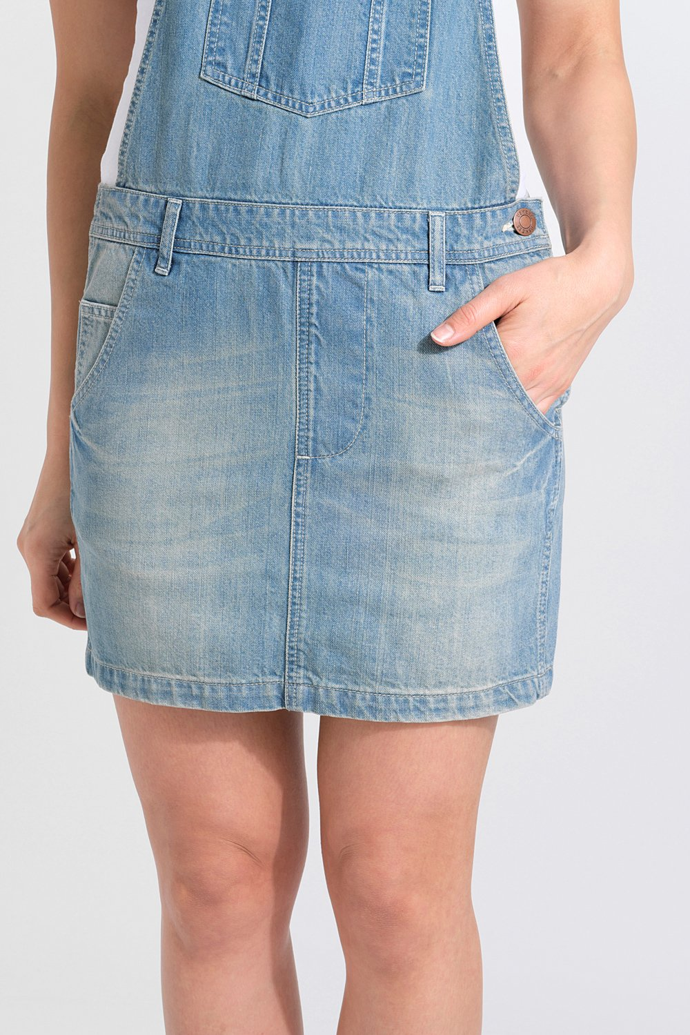 Close-up of short denim dungaree dress focussing on aged blue denim texture, belt loops and front pockets.