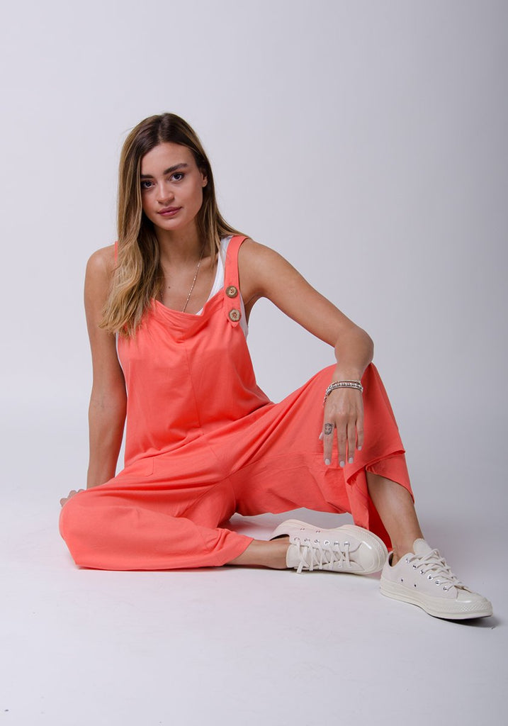 Sitting pose wearing Amber-style, coral cotton jersey, wide-leg overall.